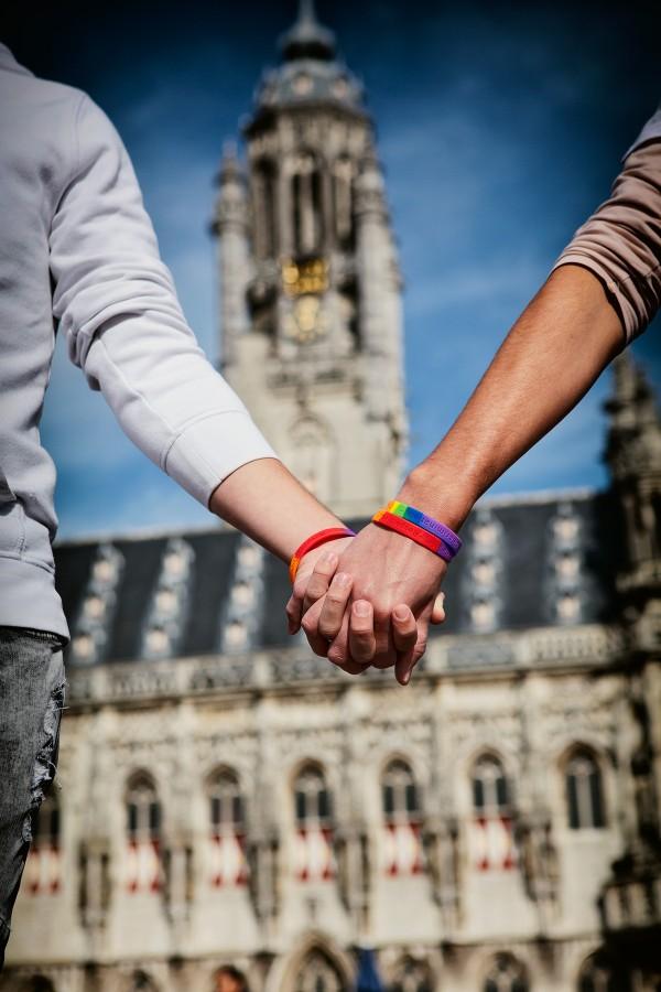 Twee mensen houden handen vast voor het oude stadhuis van Middelburg.